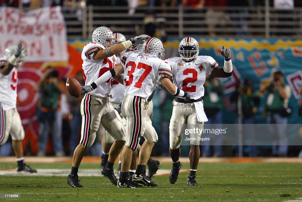 Wide receiver Jamal Luke #37 and strong safety Michael Doss #2 of the Ohio State Buckeyes celebrate with teammates during the BCS championship game against the University of Miami Hurricanes in the Tostitos Fiesta Bowl at Sun Devil Stadium on January 3, 2003 in Tempe, Arizona. Ohio State won the game 31-24 in double-overtime, winning the NCAA National Championship.