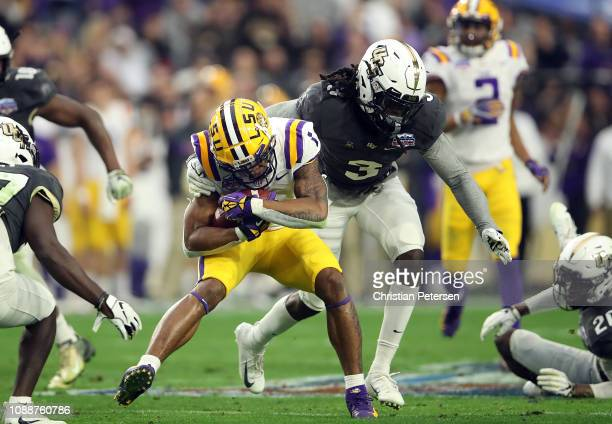 Wide receiver Ja'Marr Chase of the LSU Tigers is hit by defensive back Antwan Collier of the UCF Knights during the second quarter of the PlayStation...