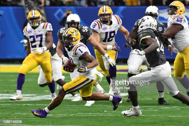 Wide receiver Ja'Marr Chase of the LSU Tigers runs past defensive back Nevelle Clarke of the UCF Knights during the PlayStation Fiesta Bowl between...