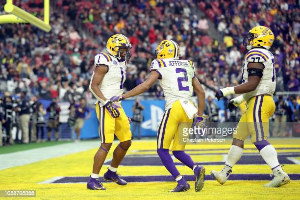 Wide receiver Ja'Marr Chase reacts with teammates wide receiver Justin Jefferson and offensive tackle Saahdiq Charles of the LSU Tigers after scoring...