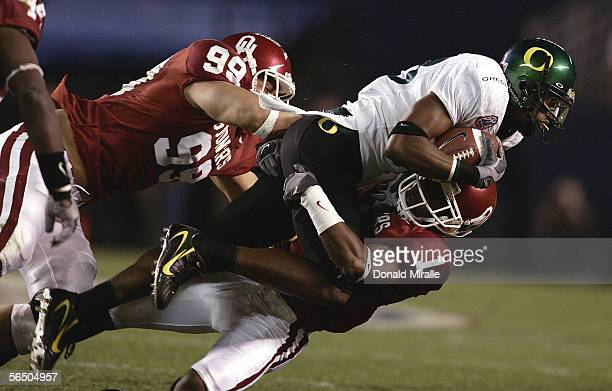 Wide receiver James Finley of the Oregon Ducks gets tackled by CJ Ah You and Reggie Smith of the Oklahoma Sooners during the first half of the...