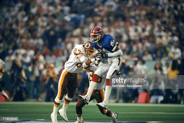 Wide Receiver James Lofton of the Buffalo Bills catches the ball mid-air and is tackled by the Washington Redskins during Super Bowl XXVI at the...