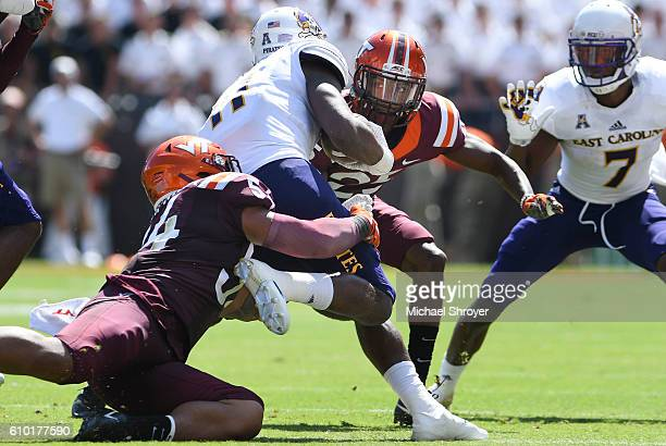 Wide receiver James Summers of the East Carolina Pirates is tackled by linebacker Andrew Motuapuaka and defensive back Greg Stroman of the Virginia...