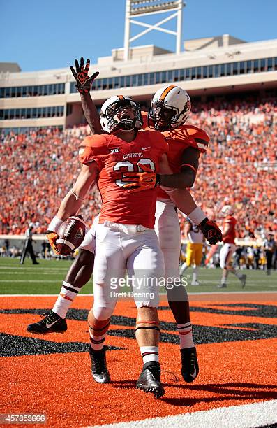 Wide receiver James Washington of the Oklahoma State Cowboys jumps on fullback Teddy Johnson after he scored a touchdown during the game against the...