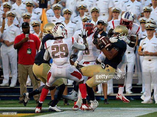 Wide receiver Jamir Tillman of the Navy Midshipmen catches a last second pass out of bounds while being defended by defensive back Gareef Glashen of...