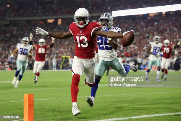 Wide receiver Jaron Brown of the Arizona Cardinals attempts to score a touchdown ahead of safety Xavier Woods of the Dallas Cowboys during the NFL...