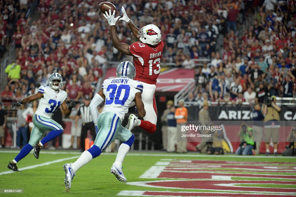 Wide receiver Jaron Brown #13 of the Arizona Cardinals catches a touchdown over cornerback Anthony Brown #30 of the Dallas Cowboys during the first quarter of the NFL game at the University of Phoenix Stadium on September 25, 2017 in Glendale, Arizona.