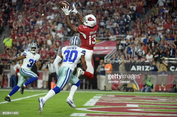 Wide receiver Jaron Brown of the Arizona Cardinals catches a touchdown over cornerback Anthony Brown of the Dallas Cowboys during the first quarter...