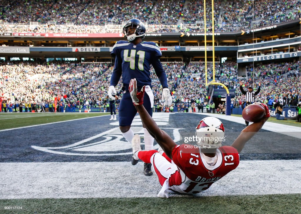 Wide receiver Jaron Brown #13 of the Arizona Cardinals celebrates his 25 yard touchdown catch against cornerback Byron Maxwell #41 of the Seattle Seahawks during the first quarter at CenturyLink Field on December 31, 2017 in Seattle, Washington.