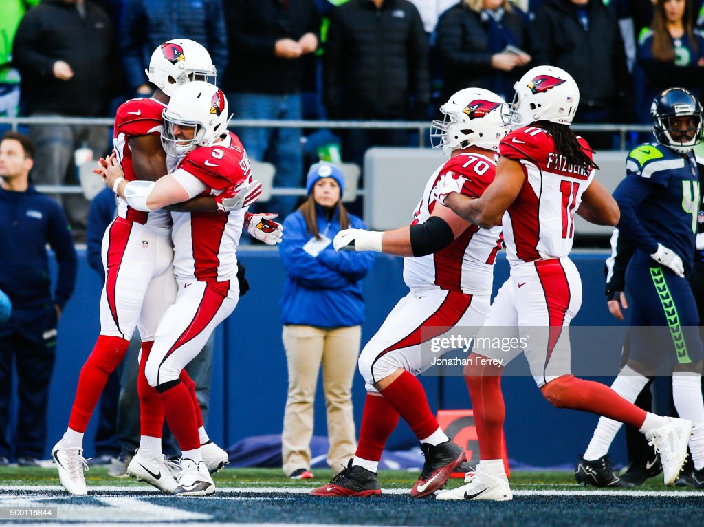 Wide receiver Jaron Brown #13 of the Arizona Cardinals is greeted by Drew Stanton #5 after scoring a 25 yard touchdown against the Seattle Seahawks in the first quarter at CenturyLink Field on December 31, 2017 in Seattle, Washington.
