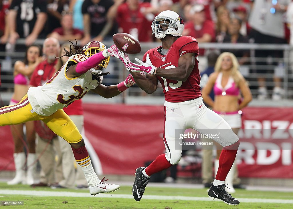 Wide receiver Jaron Brown #13 of the Arizona Cardinals is unable to catch a pass ahead of free safety E.J. Biggers #30 of the Washington Redskins during the NFL game at the University of Phoenix Stadium on October 12, 2014 in Glendale, Arizona. The Cardinals defeated the Redskins 30-20.