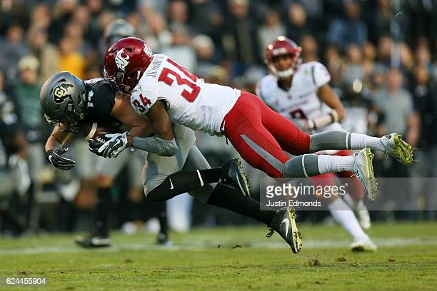 Wide receiver Jay MacIntyre of the Colorado Buffaloes is tackled by safety Jalen Thompson of the Washington State Cougars after making a catch during...