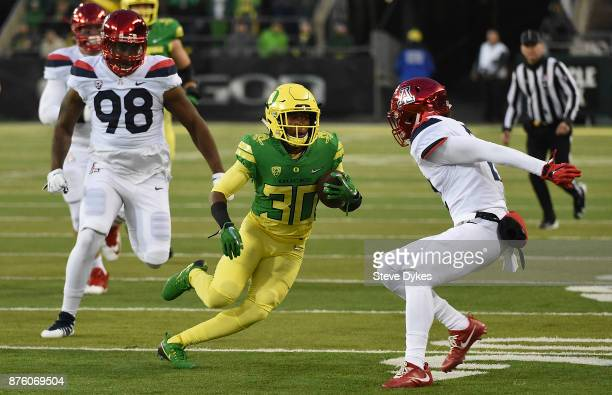 Wide receiver Jaylon Redd of the Oregon Ducks runs with the ball as defensive lineman Larry Tharpe Jr #98 of the Arizona Wildcatsgives chase during...