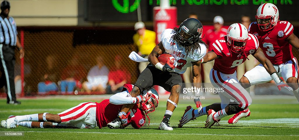 Wide receiver J.D. McKissic #23 of the Arkansas State Red Wolves is wrapped up by Defensive back Josh Mitchell and linebacker Zaire Anderson #8 of the Nebraska Cornhuskers during their game at Memorial Stadium on September 15, 2012 in Lincoln, Nebraska.