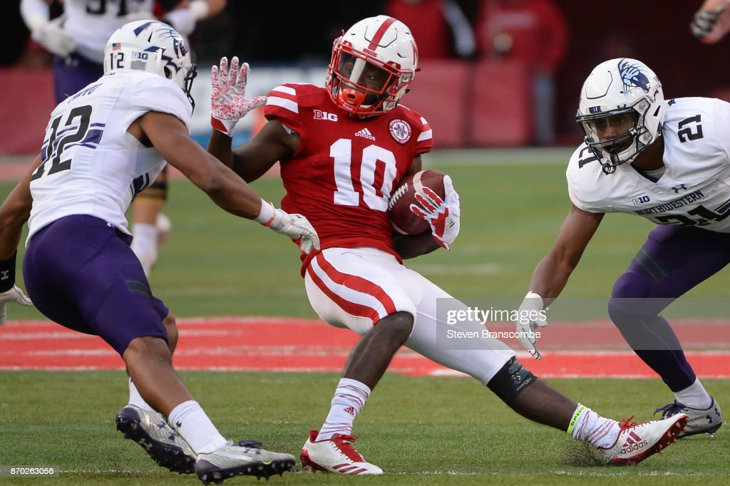 Wide receiver JD Spielman #10 of the Nebraska Cornhuskers tries to avoid the tackle from defensive back Alonzo Mayo #12 of the Northwestern Wildcats and safety Kyle Queiro #21 at Memorial Stadium on November 4, 2017 in Lincoln, Nebraska.