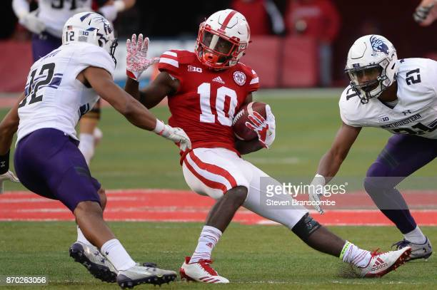 Wide receiver JD Spielman of the Nebraska Cornhuskers tries to avoid the tackle from defensive back Alonzo Mayo of the Northwestern Wildcats and...