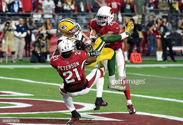Wide receiver Jeff Janis of the Green Bay Packers hauls in the gametying pass at the end of regulation while being hit by cornerback Patrick Peterson...