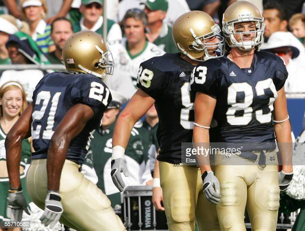 Wide receiver Jeff Samardzija of the Notre Dame Fighting Irish stands in the end zone after scoring a touchdown as teammates Anthony Fasano and...
