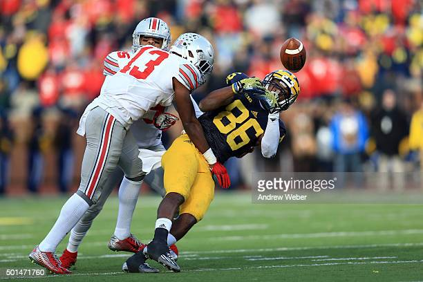 Wide receiver Jehu Chesson of the Michigan Wolverines looks to make a catch while cornerback Eli Apple of the Ohio State Buckeyes defends during the...