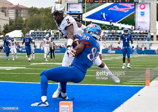 Wide receiver Jeremiah Booker of the Kansas Jayhawks catches a touchdown pass against cornerback Tanner McCalister of the Oklahoma State Cowboys in...