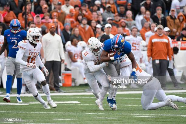 Wide receiver Jeremiah Booker of the Kansas Jayhawks is tackled by PJ Locke III and linebacker Anthony Wheeler of the Texas Longhorns at Memorial...