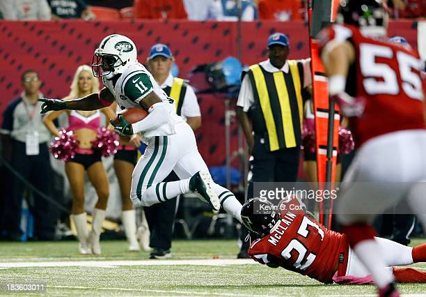 Wide receiver Jeremy Kerley of the New York Jets breaks a tackle by cornerback Robert McClain of the Atlanta Falcons to score a touchdown during...