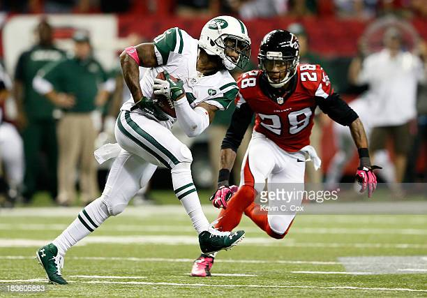 Wide receiver Jeremy Kerley of the New York Jets makes a catch as free safety Thomas DeCoud of the Atlanta Falcons defends during their game at the...