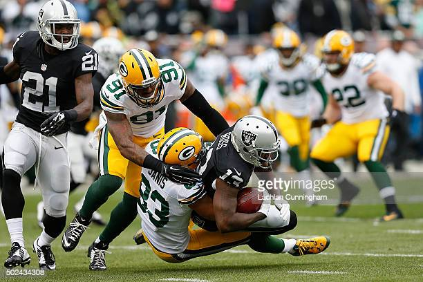 Wide receiver Jeremy Ross of the Oakland Raiders is tackled by wide receiver Jeff Janis and line backer Jayrone Elliott the Green Bay Packers in the...