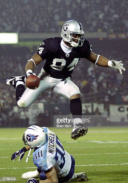 Wide receiver Jerry Porter of the Oakland Raiders hurdles over cornerback Donald Mitchell of the Tennessee Titans after making a catch in the fourth...