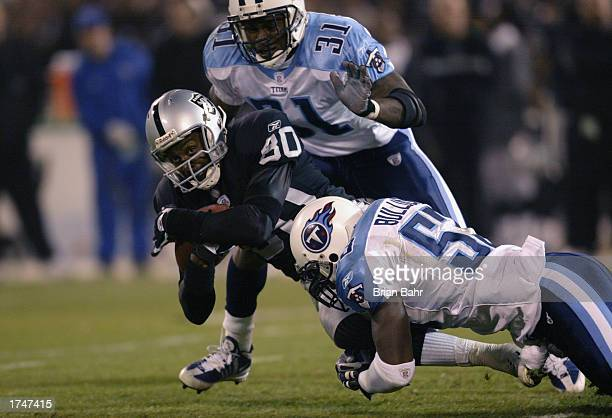 Wide receiver Jerry Rice of the Oakland Raiders holds tight while tackled by linebacker Keith Bulluck of the Tennessee Titans during the AFC...
