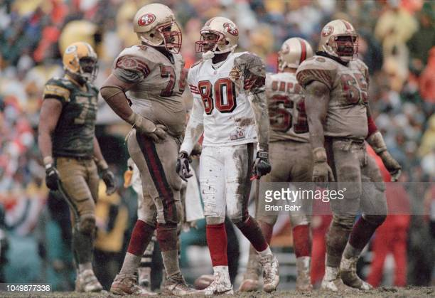 Wide receiver Jerry Rice of the San Francisco 49ers confers with teammates Ray Brown and Steve Wallace during the NFC Divisional playoff game against...