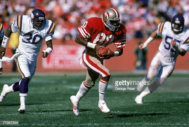 Wide receiver Jerry Rice of the San Francisco 49ers runs with the ball away from Minnesota Vikings cornerback Issiac Holt and linebacker Scott...