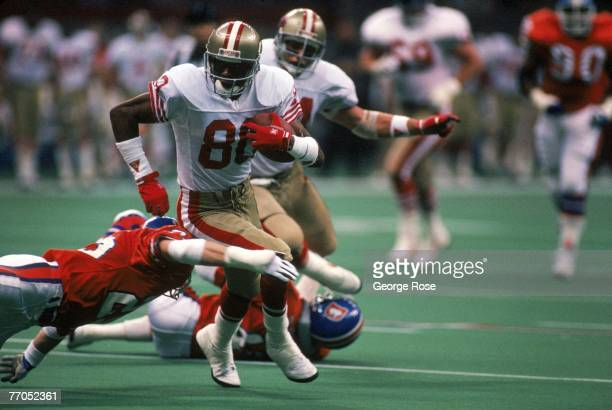 Wide receiver Jerry Rice of the San Francisco 49ers tries to outrun a diving tackle attempt by Denver Broncos defensive back Kip Corrington during a...