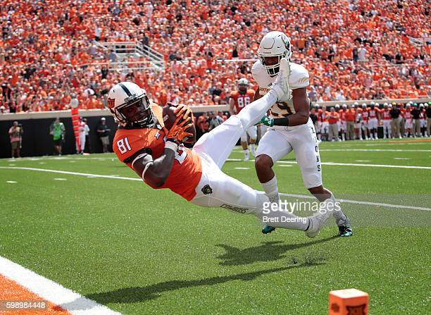 Wide receiver Jhajuan Seales of the Oklahoma State Cowboys catches a pass near the end zone in front of defensive back Courtney Rutledge of the...