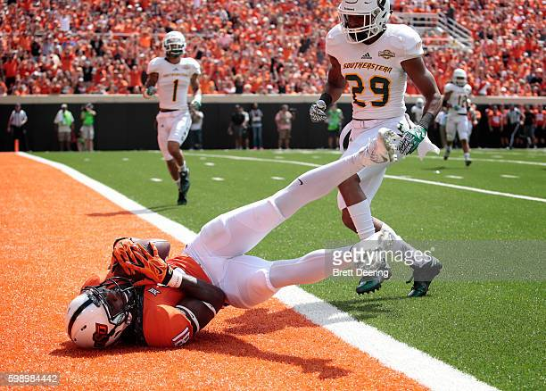 Wide receiver Jhajuan Seales of the Oklahoma State Cowboys scores in front of defensive back Courtney Rutledge of the Southeastern Louisiana Lions...