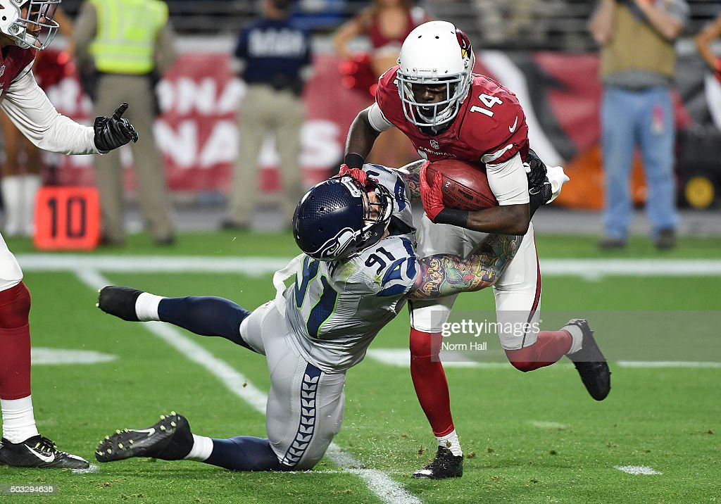 Wide receiver J.J. Nelson #14 of the Arizona Cardinals is tackled by defensive end Cassius Marsh #91 of the Seattle Seahawks in the second half of the NFL game at University of Phoenix Stadium on January 3, 2016 in Glendale, Arizona. The Seahawks defeated the Cardinals 36-6.