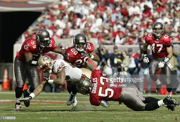 Wide receiver JJ Stokes of the San Francisco 49ers is tackled by Derrick Brooks Ronde Barber and Shelton Quarles of the Tampa Bay Buccaneers in the...