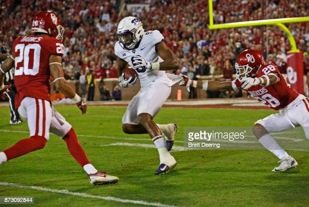 Wide receiver John Diarse of the TCU Horned Frogs tries to evade safety Robert Barnes and safety Chanse Sylvie of the Oklahoma Sooners at Gaylord...