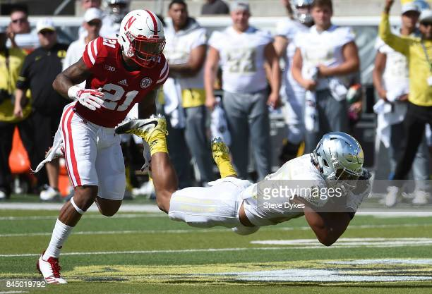 Wide receiver Johnny Johnson III of the Oregon Ducks catches a pass in front of Lamar Jackson of the Nebraska Cornhuskers during the second quarter...