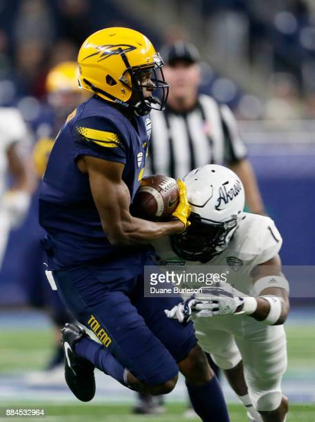 Wide receiver Jon'Vea Johnson of the Toledo Rockets catch a pass against cornerback Alvin Davis of the Akron Zips during the first half at Ford Field...