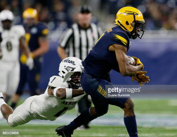Wide receiver Jon'Vea Johnson of the Toledo Rockets is tackled by cornerback Alvin Davis of the Akron Zips during the first half at Ford Field on...