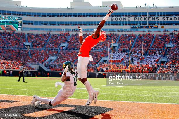 Wide receiver Jordan McCray of the Oklahoma State Cowboys can't get his hand around a pass to the endzone against cornerback Kalon Barnes of the...