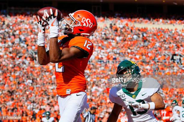 Wide receiver Jordan McCray of the Oklahoma State Cowboys wraps his hands around a touchdown pass over his shoulder against cornerback Raleigh Texada...