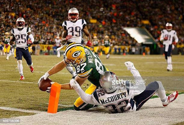 Wide receiver Jordy Nelson of the Green Bay Packers reaches out with the football over free safety Devin McCourty of the New England Patriots to...