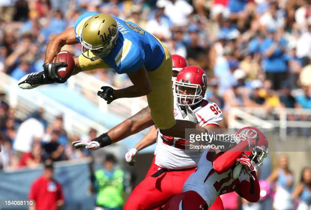 Wide receiver Joseph Fauria of the UCLA Bruins jumps over defensive back Eric Rowe of the Utah Utes after making a catch in the first quarter at the...