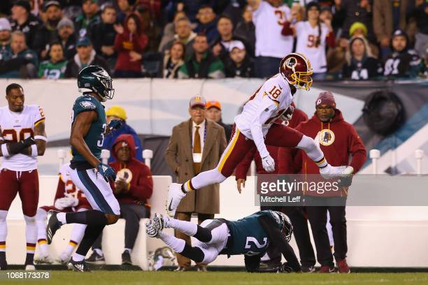 Wide receiver Josh Doctson of the Washington Redskins leaps in the air as he runs with the ball and knocked out of bounds by safety Corey Graham of...