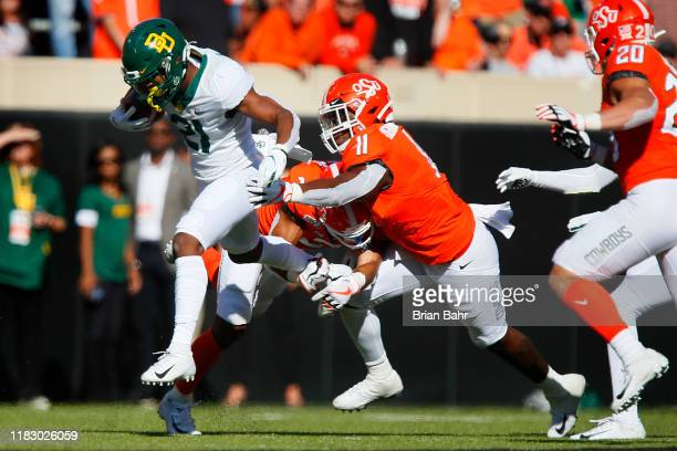 Wide receiver Josh Fleeks of the Baylor University Bears runs for eight yards against linebacker Amen Ogbongbemiga and safety Tre Sterling of the...