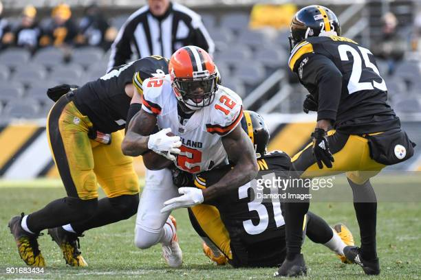 Wide receiver Josh Gordon of the Cleveland Browns is tackled by linebacker TJ Watt cornerbacks Mike Hilton and Artie Burns of the Pittsburgh Steelers...