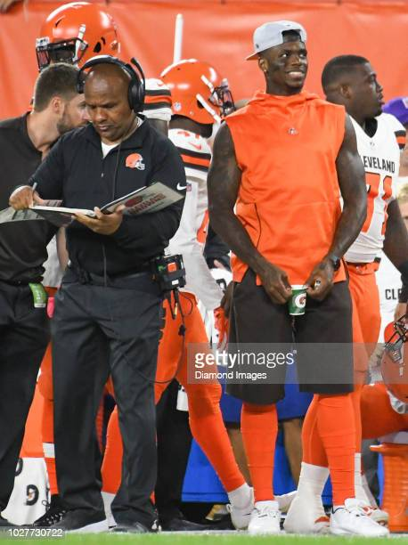 Wide receiver Josh Gordon of the Cleveland Browns watches the action from the sideline as head coach Hue Jackson reads through a notebook in the...