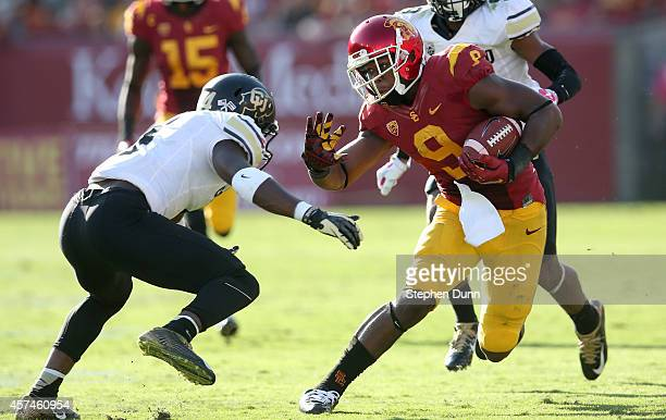 Wide receiver JuJu Smith of the USC Trojans carries the ball against defensive back Chidobe Awuzie of the Colorado Buffaloes at Los Angeles Memorial...